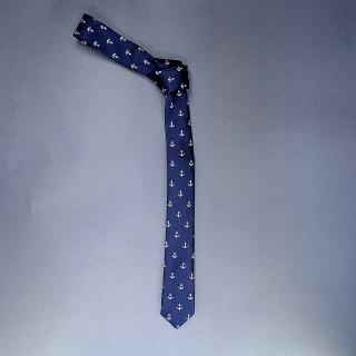 Недорогой узкий мужской галстук синего цвета с рисунками в виде якорей.